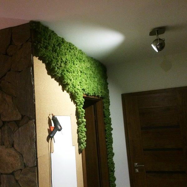 Wyklejanie zielonej ściany w domu.